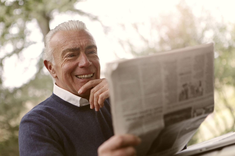 Älterer Herr mit Zeitung im Freien