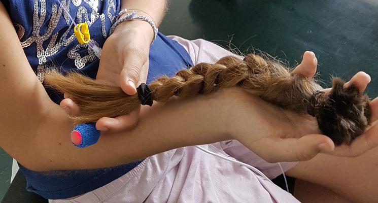 Ein Mädchen mit einem geflochtenem Zopf im Arm