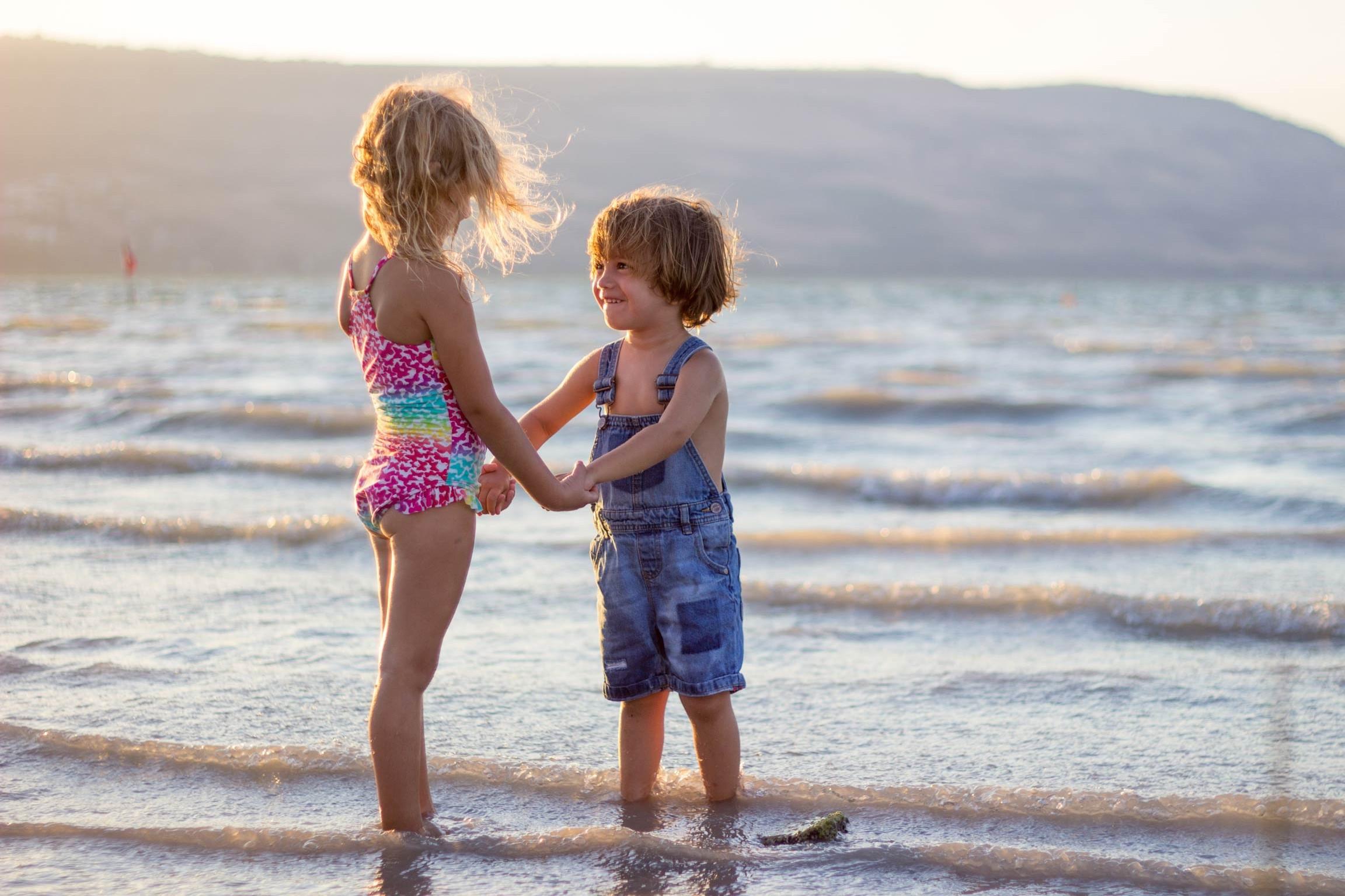 Zwei Kinder am Strand, halten sich an den Händen