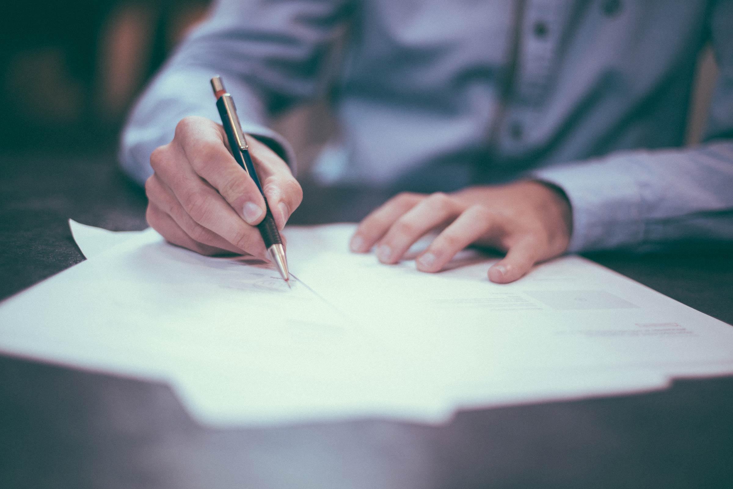 Ein Mann unterzeichnet Dokumente