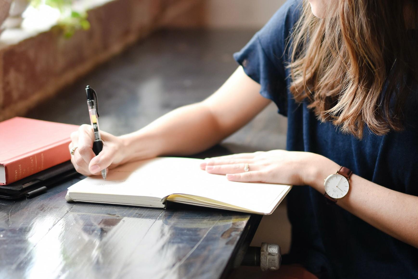 Eine junge Frau mit Stift und Notizbuch